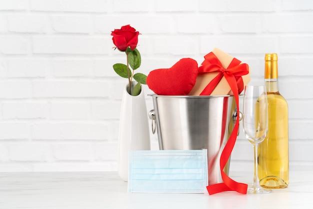 Valentinstagfeier mit wein-, blumenstrauß- und gesichtsmaskenschutzkonzept während dieser schweren zeit.