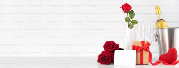 Valentinstagfeier mit wein, geschenk und rosenstrauß zum feiertagsgruß.
