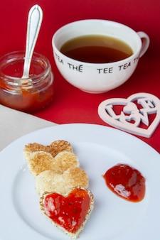 Valentinstagfrühstück auf rotem hintergrund und tee