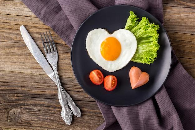 Valentinstagfrühstück mit herzförmigen spiegeleiern auf grauem teller. flach liegen, draufsicht