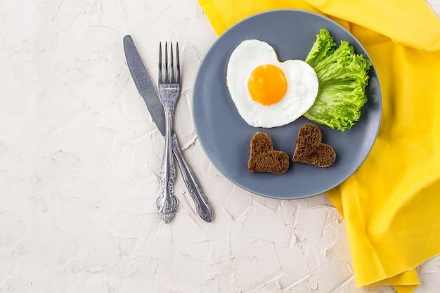 Valentinstagfrühstück mit herzförmigen spiegeleiern auf grauem teller und gelber serviette