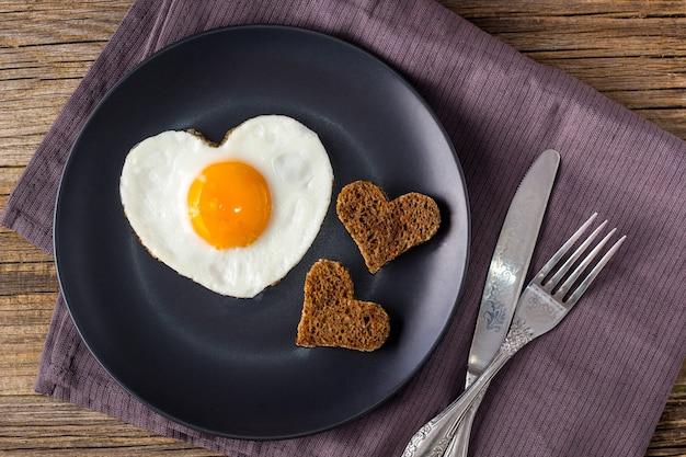 Valentinstagfrühstück mit herzförmigen spiegeleiern auf grauem teller und serviette