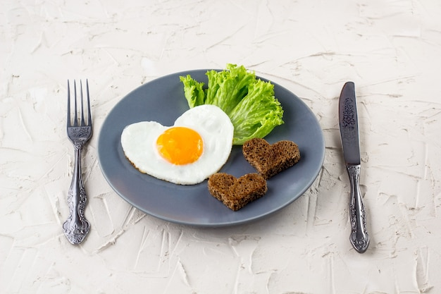 Valentinstagfrühstück mit herzförmigen spiegeleiern auf grauem teller