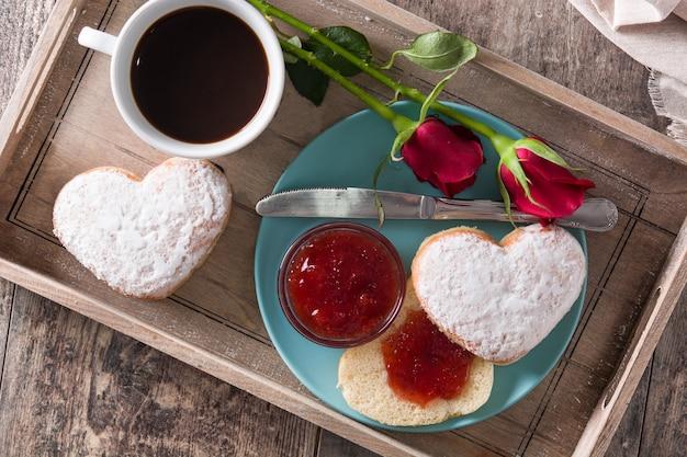 Valentinstagfrühstück mit kaffee, herzförmigem brötchen, beerenmarmelade und rosen auf einem behälter, draufsicht