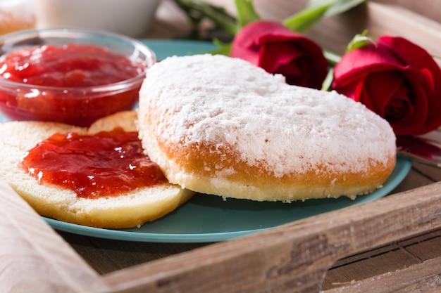 Valentinstagfrühstück mit kaffee, herzförmigem brötchen, beerenmarmelade und rosen auf einem tablett. nahansicht