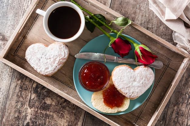 Valentinstagfrühstück mit kaffee, herzförmigem brötchen, beerenmarmelade und rosen auf einem tablett