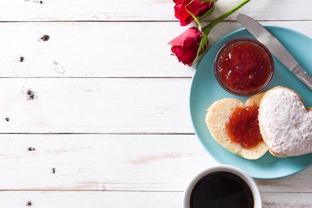 Valentinstagfrühstück mit kaffee, herzförmigem brötchen, beerenmarmelade und rosen