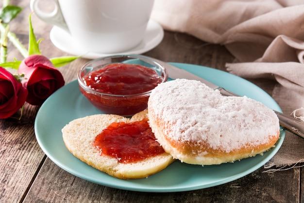 Valentinstagfrühstück mit kaffee, herzförmigem brötchen und beerenmarmelade.