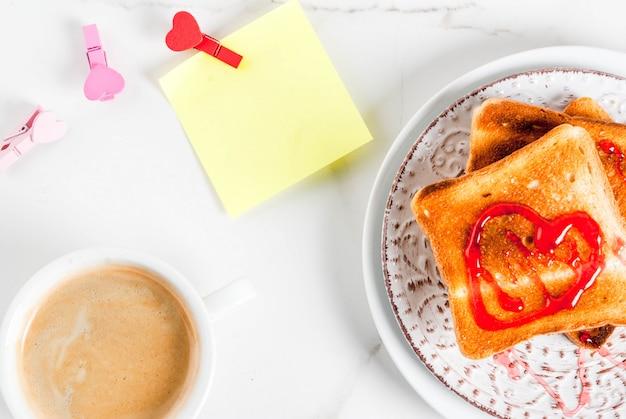 Valentinstagfrühstücksidee mit kaffeetasse, toastbrot mit roter erdbeermarmelade
