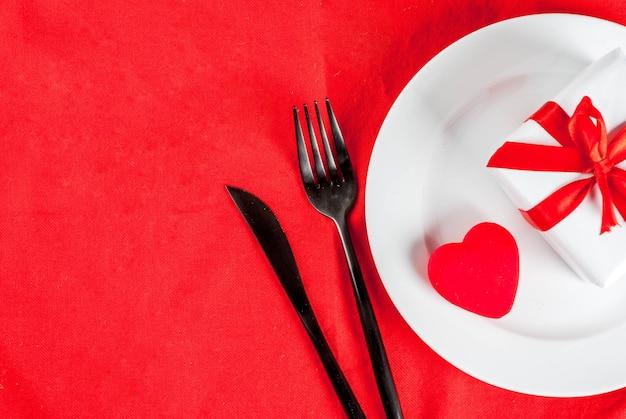 Valentinstaggedeck mit platte, gabel, messer, geschenkbox und rotem herzen, auf draufsicht der roten tischdeckenszene