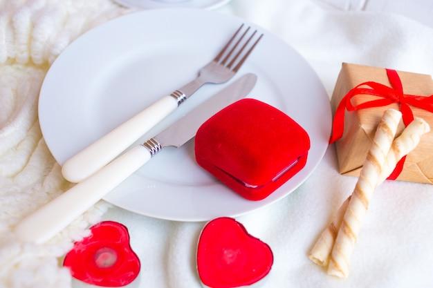 Valentinstaggedeck mit rotem samtringkasten, kerzen und tafelsilber