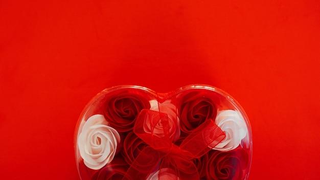 Valentinstaggeschenk auf rotem grund. viele rote und weiße rosen in einem herzförmigen paket, gebunden mit einem roten band. das konzept der liebe
