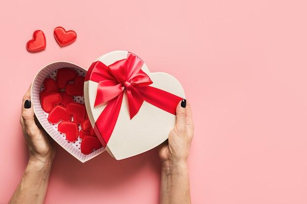 Valentinstaggeschenk in der hand der frau mit roten kleinen herzen auf rosa.