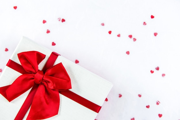 Valentinstaggeschenkbox auf weißbuchhintergrund mit roten herzformen