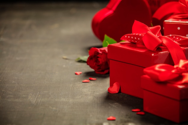 Valentinstaggeschenkbox geschenke mit rotem bogen auf dem hölzernen hintergrund