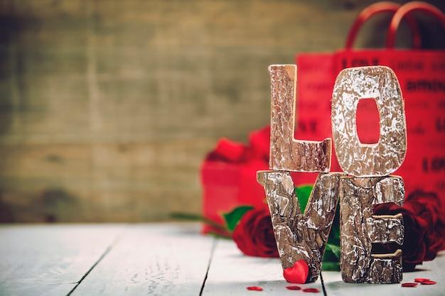 Valentinstaggeschenkbox lieben sie hölzerne buchstaben auf rustikalem hintergrund