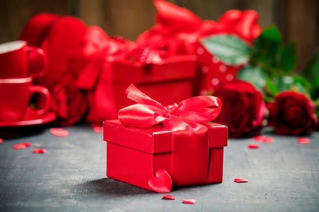Valentinstaggeschenkbox valentinsgrußgeschenkboxen gebunden mit einem roten satinbandbogen und schönen rosen auf rustikalem hintergrund.