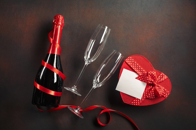 Valentinstaggrußkarte mit champagnergläsern und süßigkeitsherzen auf steinhintergrund.