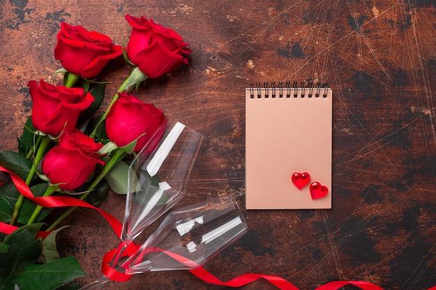 Valentinstaggrußkarte mit rotrosenblumen und champagnergläsern auf hölzernem hintergrund