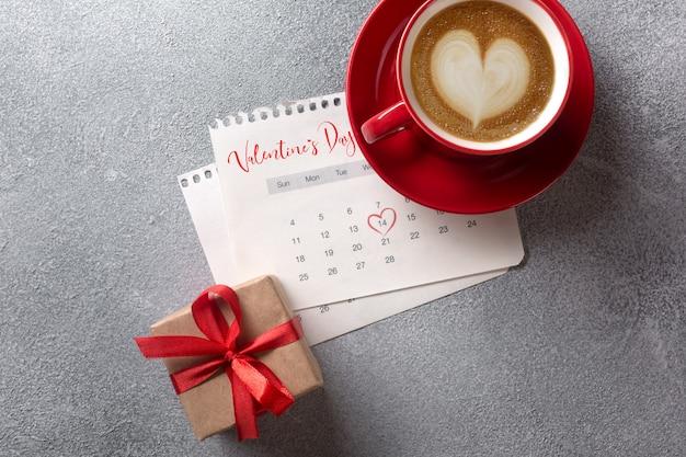 Valentinstaggrußkarte. rote kaffeetasse und geschenkbox über februar-kalender. ansicht von oben