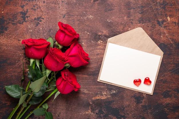 Valentinstaggrußkarte rotrose blüht blumenstrauß und handwerksumschlag mit roten herzen auf einem hölzernen hintergrund der weinlese