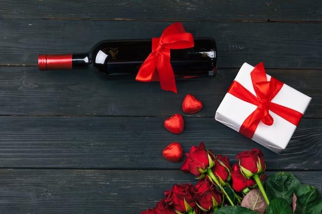 Valentinstaggrußkarte, rotrosenblumen, wein und geschenkbox auf holztisch.