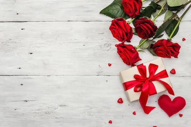 Valentinstaggrußkartenhintergrund mit geschenkboxen, frischen burgunderrosen und verschiedenen herzen. alter weißer holztisch. hochzeits- oder geburtstagskonzept, platz für text, flache lage