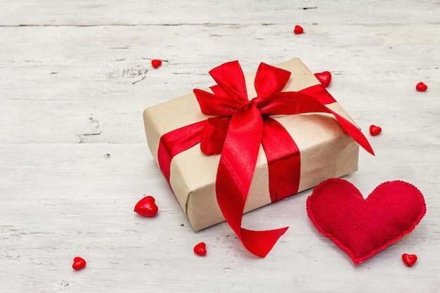Valentinstaggrußkartenhintergrund mit geschenkboxen, roten bändern und verschiedenen herzen. alter weißer holzbretterhintergrund. hochzeits- oder geburtstagskonzept, flache lage, platz für text