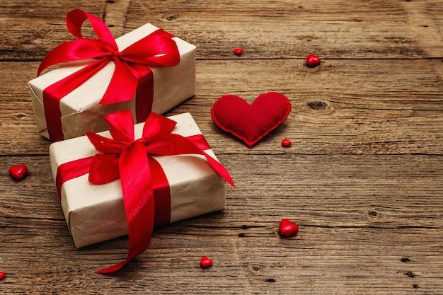 Valentinstaggrußkartenhintergrund mit geschenkboxen, roten bändern und verschiedenen herzen. vintage holztisch. hochzeits- oder geburtstagskonzept, platz für text, flache lage