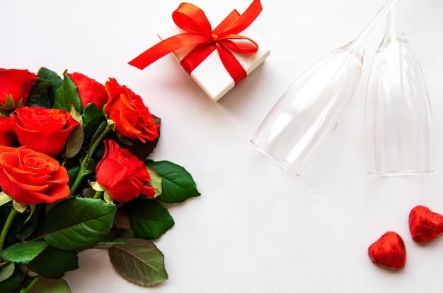 Valentinstaghintergrund der roten rosen und der gläser