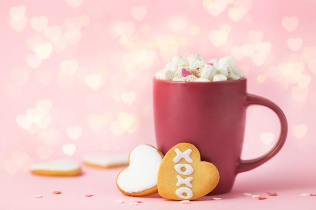 Valentinstaghintergrund mit bokeh licht. rote tasse mit kakao, marshmallows und keksen