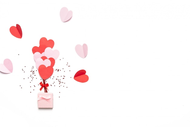 Valentinstaghintergrund mit den roten und rosa herzen mögen die ballone, die auf weißem hintergrund, draufsicht lokalisiert werden