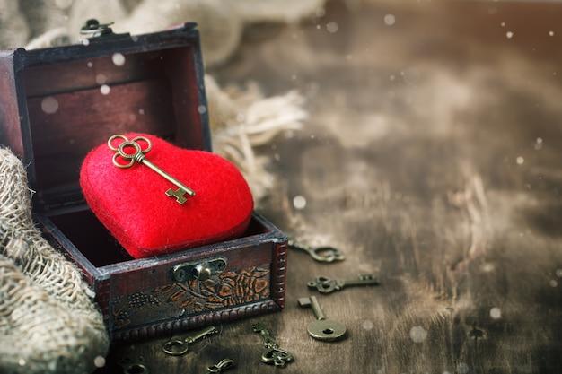 Valentinstaghintergrund mit einem herzen und einem alten schlüssel auf holztisch.