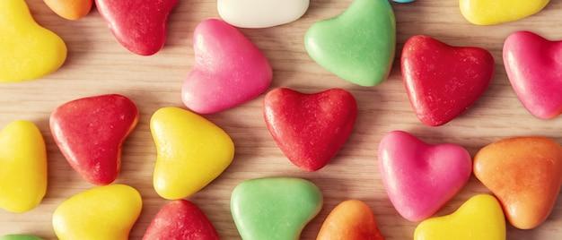 Valentinstaghintergrund mit herzen formte auf einen holztisch