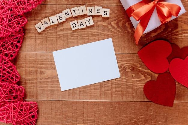 Valentinstaghintergrund mit leerem grußkartengeschenk und herz