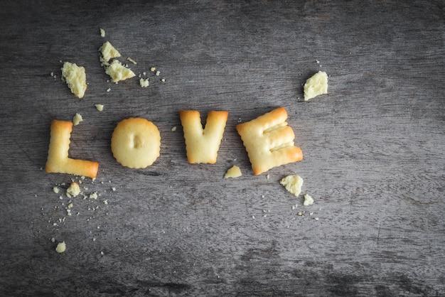 Valentinstaghintergrund mit liebesalphabet auf hölzernem brett