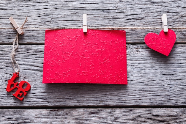 Valentinstaghintergrund mit rotem papierherz und leerer grußkarte auf wäscheklammern auf rustikalen holzbrettern. glückliches liebhaber-tageskartenmodell, kopieren sie raum
