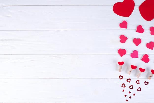Valentinstaghintergrund mit roten herzen auf hölzernem hintergrund