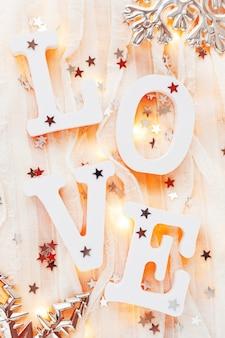 Valentinstaghintergrund mit wort liebe, dekorationen und glühlampen.