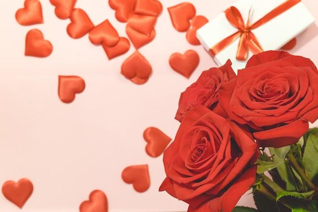 Valentinstaghintergrund, rotrose mit roten herzen und geschenkbox auf rosa hintergrund, für karten- und hochzeitshintergrund