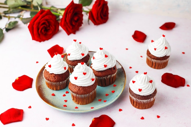 Valentinstaghintergrund, schokoladenkleine kuchen mit herzen formten süßigkeiten, draufsicht