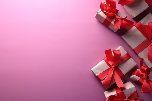 Valentinstaghintergrundgrußkarten-liebessymbole, rote dekoration mit geschenkboxen auf rosa hintergrund. draufsicht mit kopienraum und -text flache lage
