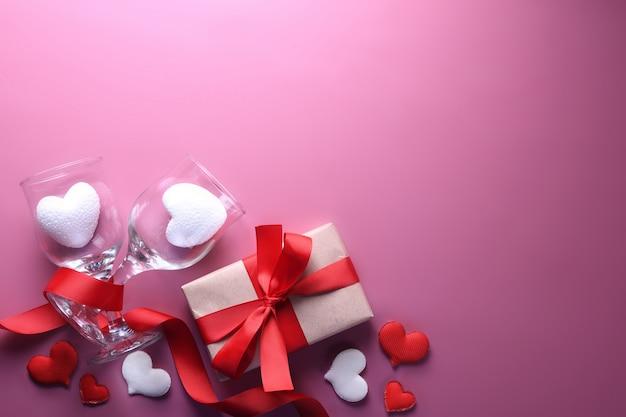 Valentinstaghintergrundgrußkarten-liebessymbole, rote dekoration mit gläsern auf rosa hintergrund. draufsicht mit kopienraum und -text flache lage