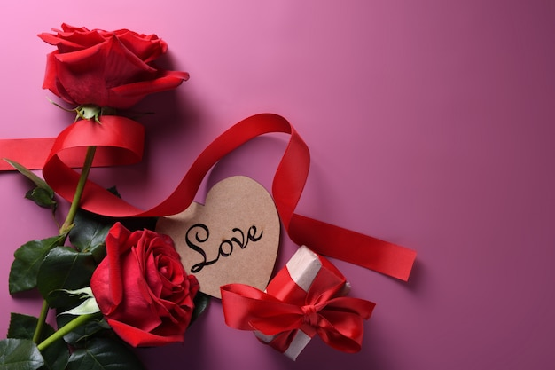 Valentinstaghintergrundgrußkarten-liebessymbole, rote dekoration mit glasherz-rosengeschenken auf rosa hintergrund. draufsicht mit kopienraum und -text flache lage