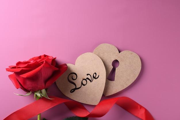 Valentinstaghintergrundgrußkarten-liebessymbole, rote dekoration mit herzen auf rosa hintergrund. draufsicht mit kopienraum und -text flache lage