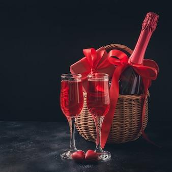 Valentinstagkarte mit champagner und rotem geschenk auf schwarzem. platz für ihre grüße.