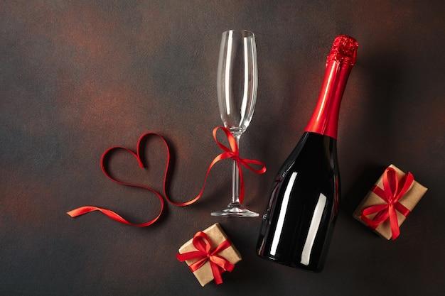 Valentinstagkarte mit gläsern champagner und geschenkboxen.