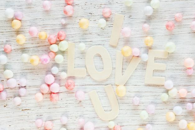 Valentinstagkarte mit ich liebe u-text und haufen von perlen auf der hölzernen, süßen getonten pastellfarbe.