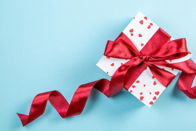 Valentinstagkonzept - geschenk mit herzen und rotem band, blaues backgound, draufsicht