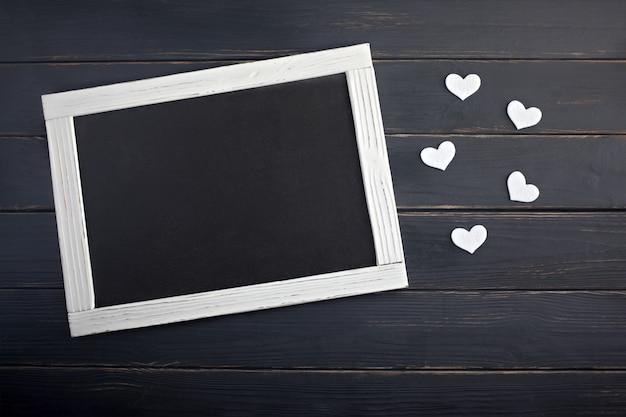 Valentinstagkonzept mit weißen herzen und tafel auf dem hölzernen hintergrund